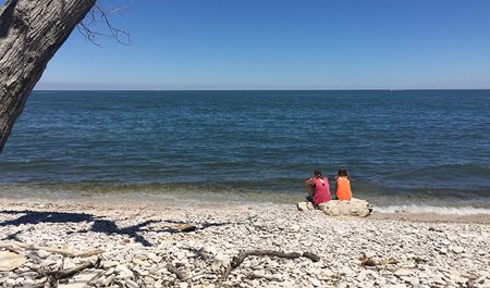 two tourists sitting on the Lake Erie shoreline